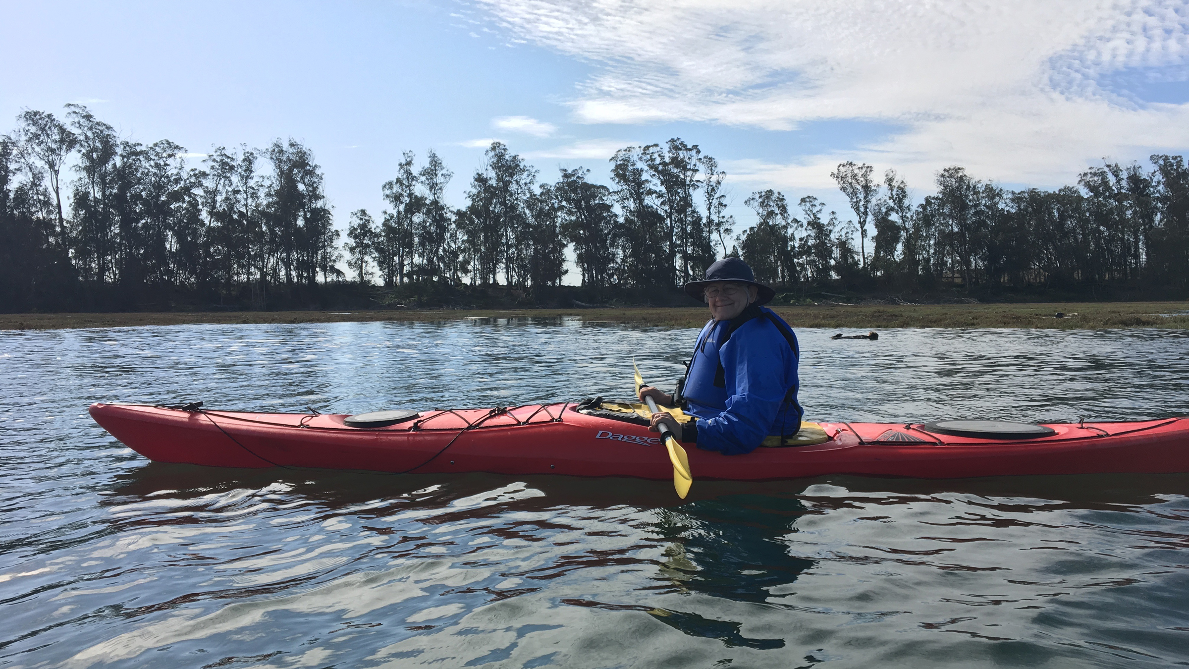 woman kayaking with an otter